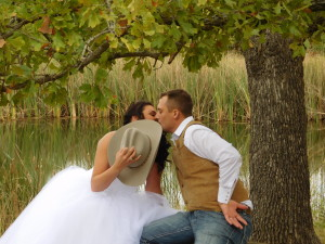 Precious couple kissing behind a cowboy hat on their wedding day sitting by a pond