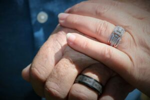 hands touching with wedding rings showing