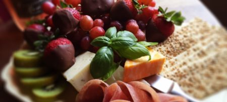 White tray piled with chocolate covered strawberries, white and orange cheeses, salami, crackers, and kiwi
