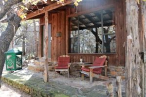 Exterior of rustic cabin with covered porch and sitting chairs, surrounded by trees