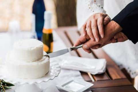 Bride and grooms hands slicing through a small white wedding cake