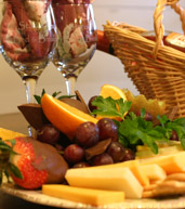 Tray of assorted fruit, cheese, a wicker basket and two wine glasses with rose colored napkins in them.