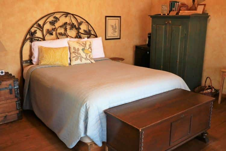 Guest room with gold walls, wood floors, arched iron headboard, nightstands and armoire
