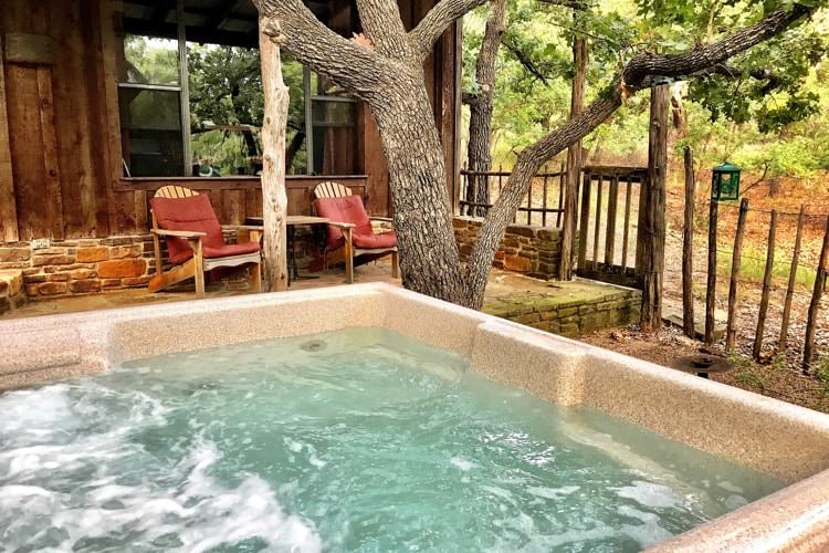 Outdoor hot tub filled with bubbling water next to a cottage with covered porch surrounded by trees