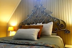 Guest bed with scrolling iron headboard, nightstands with lamps and sloped ceiling