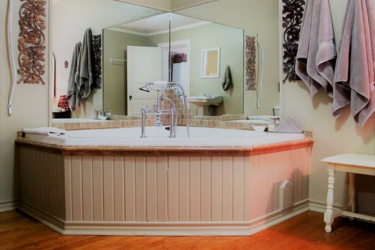 Guest bath with ivory walls, large corner soaking tub and large hanging mirrors