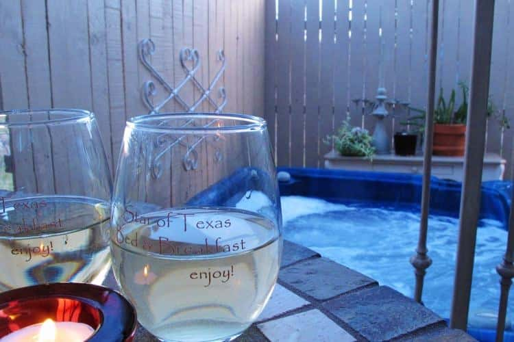 Two wine glasses next to a candle with a view of the hot tub in the background