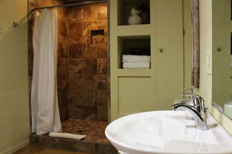 Light green guest bath with white pedestal sink, shelves, and tiled walk-in shower