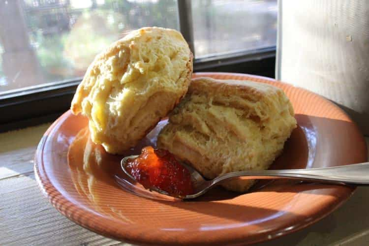 An orange plate topped with a fresh biscuit cut in half and a spoonful of red jam