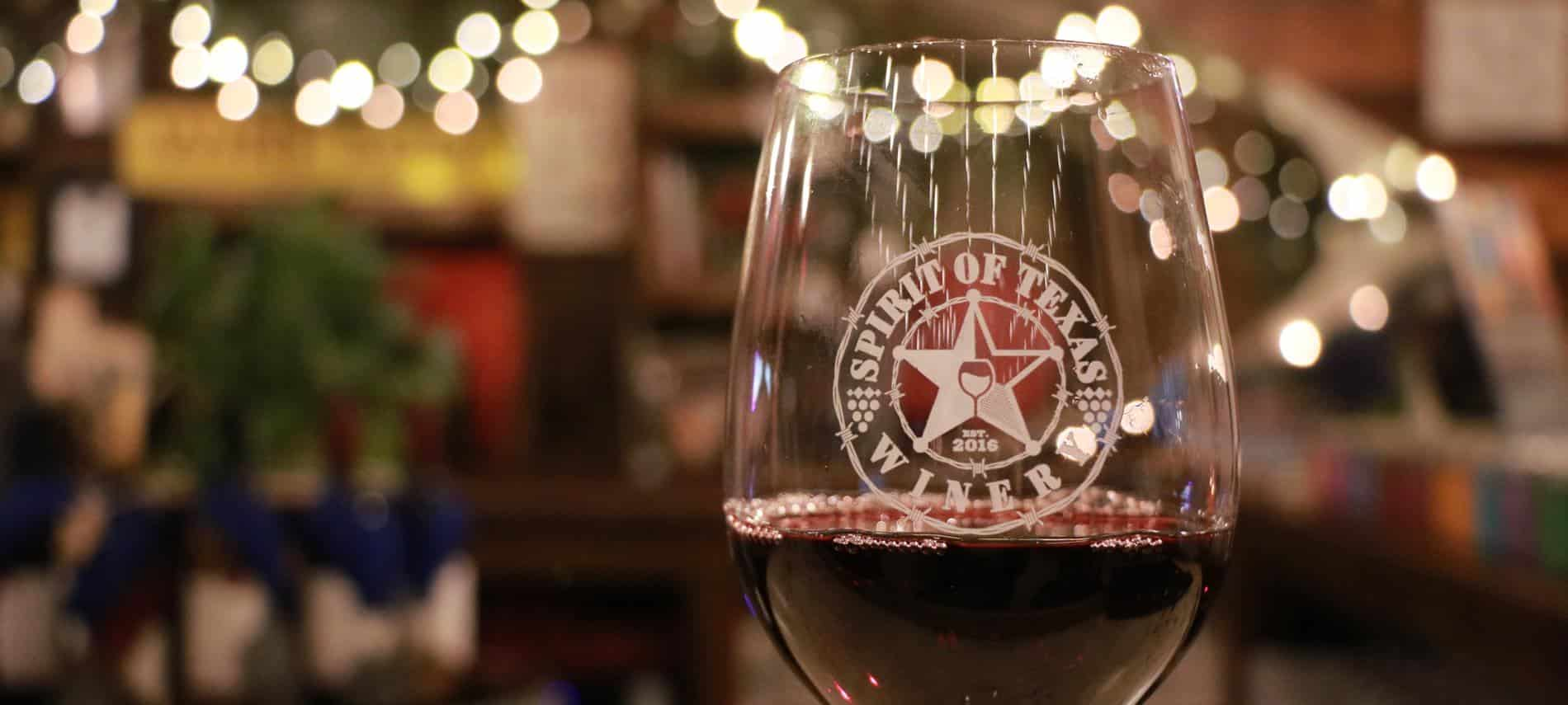 Close-up view of a Star of Texas winery glass filled with red wine and twinkle lights in the background
