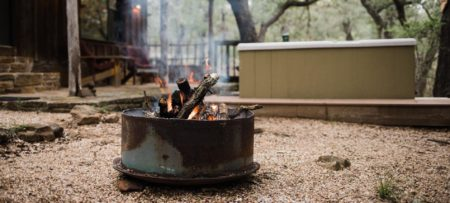 Rustic fire pit with a burning campfire outside one of the cottages