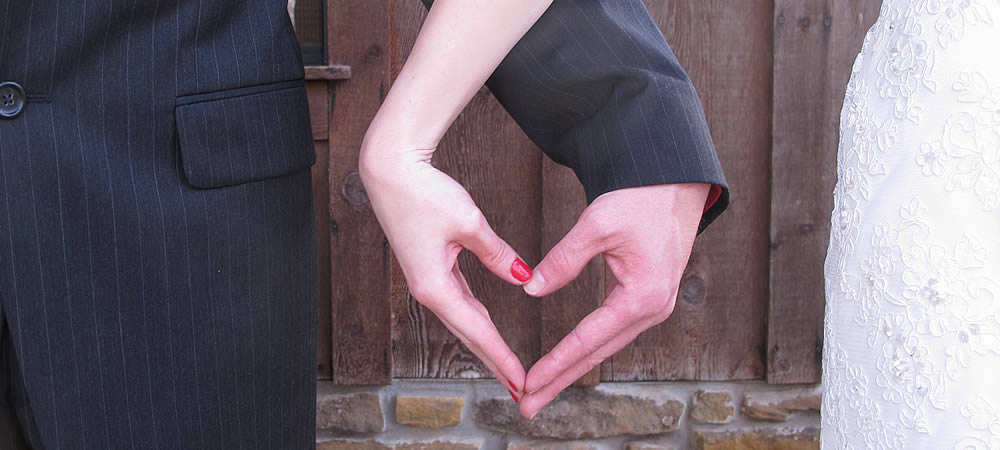 groom in black suite and bride in white gown with hands shaping a heart symbol