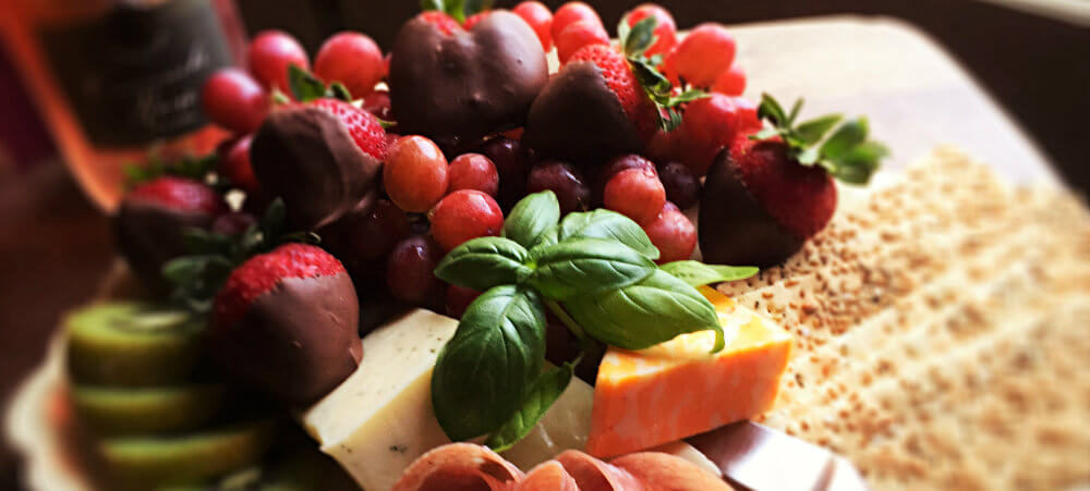 fruit and cheese platter with dark purple grapes, red chocolate strawberries and nuts and crackers