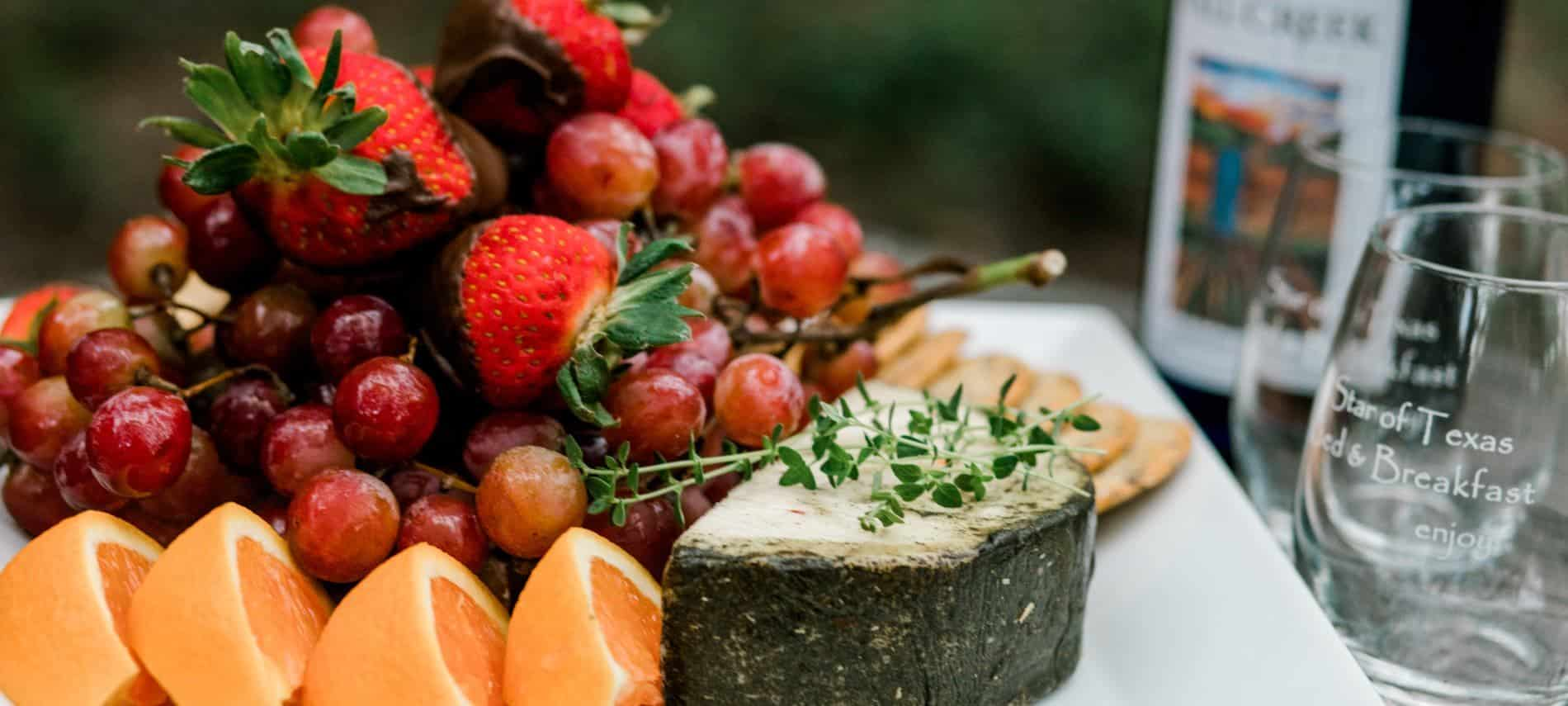 White serving tray piled with fresh grapefruit, strawberries, grapes and cheese next to a bottle of wine