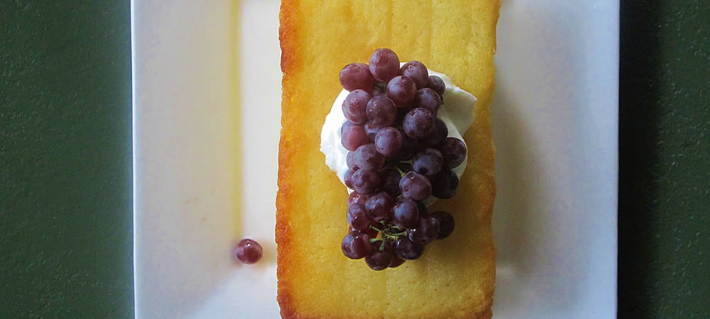 large white platter with cake topped with red grapes and white cream