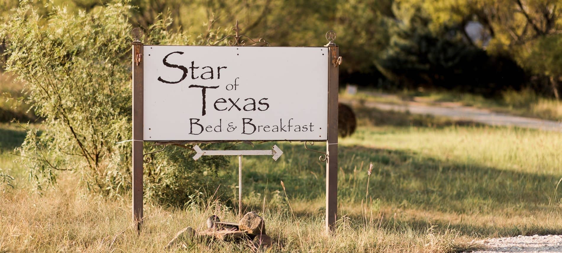 Exterior white sign with wood frame that says Star of Texas Bed & Breakfast surrounded by grass and trees