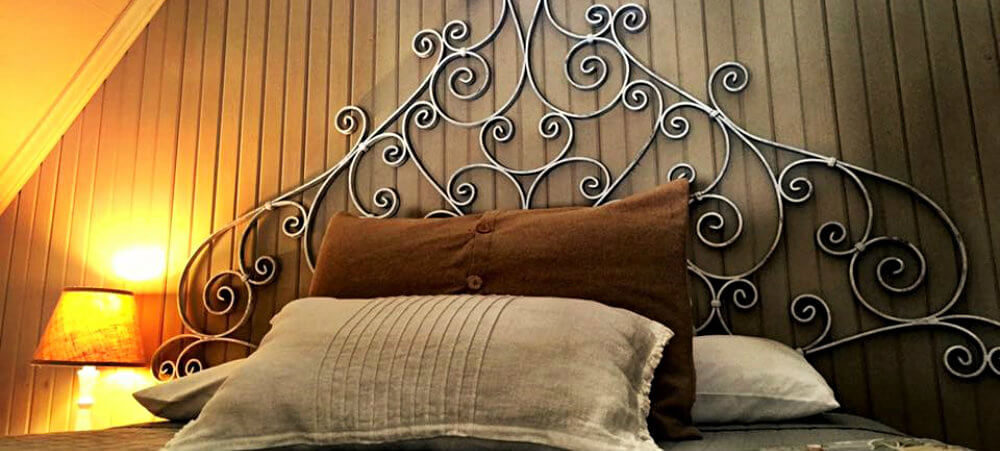 queen bed with yellow and brown floral comforter and white iron headboard