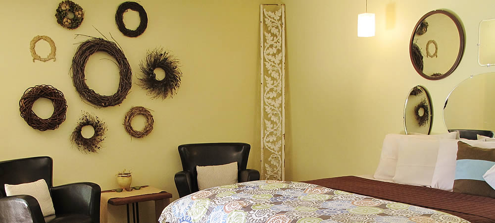 queen bed with brown and teal bedding next to brown wicker table and chairs