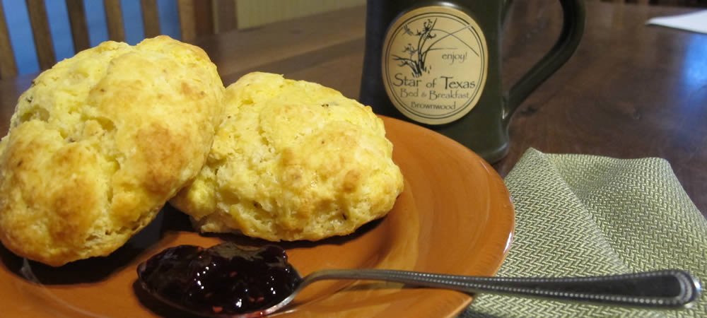 Two biscuits on a burnt orange plate with a spoonful of jelly and a green coffee mug in the background.