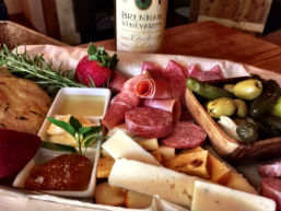 platter of meats with cheese, pickles and bottle of wine