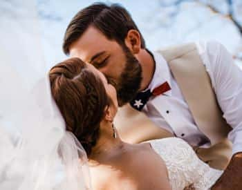 Groom in white and tan kissing his bride in a white dress outside