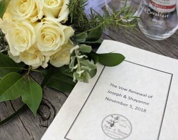 Paper vow renewal program on a table next to a bouquet of cream roses and two wine glasses
