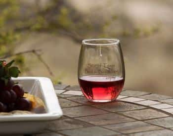 Outdoor stone table topped with a glass of red wine next to a tray of snacks