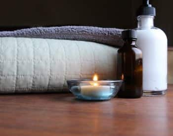 Folded white blanket and towel next to a burning tea light candle and two bottles