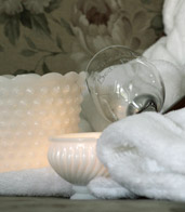 Close up of a white towel, candle, and bowl along with a wine glass and a grey floral pattern in the background.