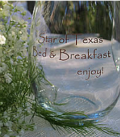 Star of Texas Bed & Breakfast engraved glass sitting on a white table with green and while flowers beside it.