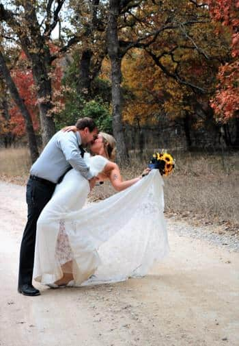 Groom dipping his bride into an embraced kiss on a dir path surrounded by colorful trees in the fall