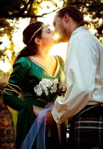 Groom and bride dressed in Scottish attire, kissing at sunset surrounded by trees