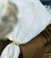 White linnen napkin gathered together with a gold and diammond wedding ring.