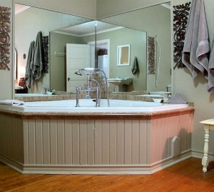 Wildrose tub that is a 70 gallon soaking tub with mirrors on the wall around it.